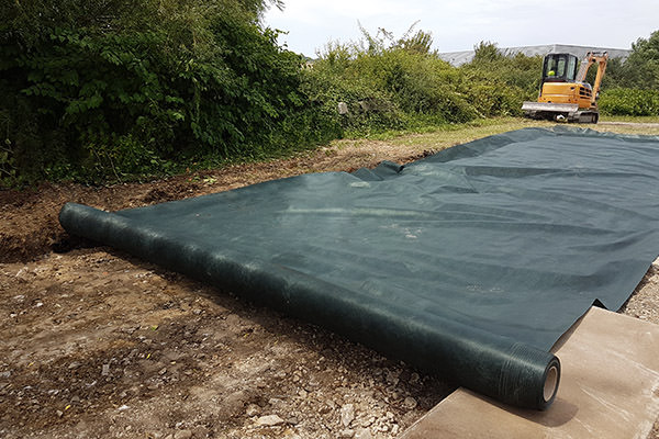 roll of weed barrier being rolled out over the ground