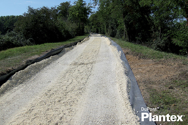 weed and root barrier being laid down on a path